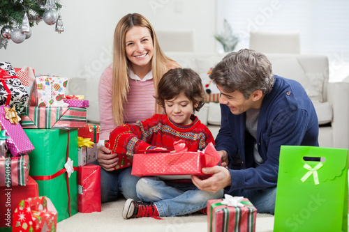 Woman With Boy And Man Opening Christmas Gift
