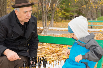 Senior man teaching his grandson chess