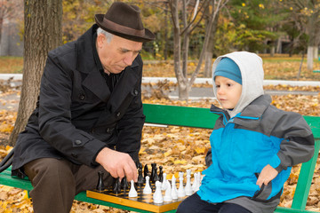 Little boy playing chess with his grandfather