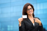 Businesswoman showing business card outside
