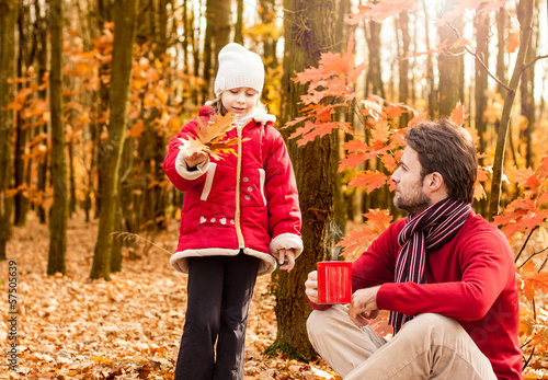 Father and daughter having fun outdoor in an autumn park