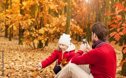 Man taking autumn outdoor picture with mobile phone