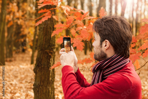 Man taking autumn outdoor photo with mobile phone