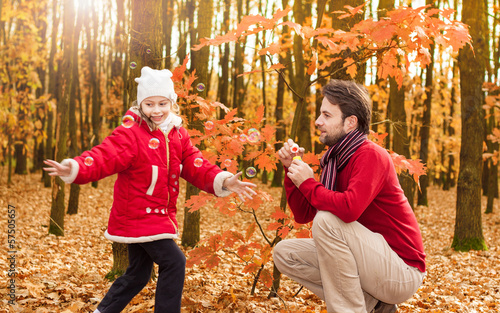 Father and daughter blowing bubbles outdoor in an autumn park