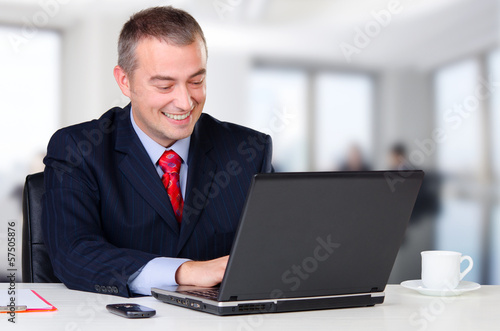 Young happy business man working on notebook
