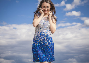 Beauty woman in a fashionable dress  on sky background.