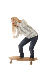 Young girl balancing on skateboard talking on cell phone