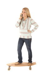 Young girl on skateboard talking on her cell phone