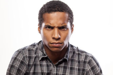 somber dark-skinned young man poses with angry expression
