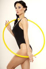 Beautiful sporty woman in black dress slim body with hula hoop