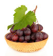 Ripe delicious grapes in wicker basket isolated on white