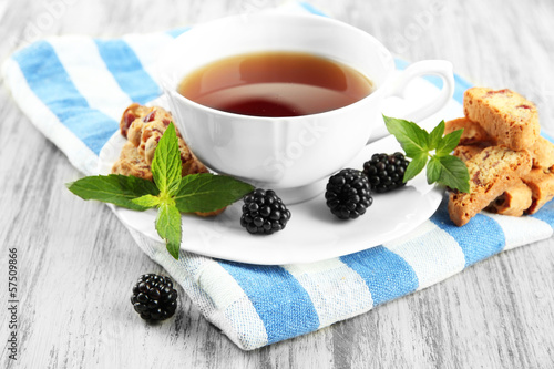Cup of tea with cookies and blackberry on table close-up
