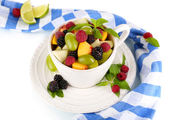 Fruit salad in cup near napkin isolated on white