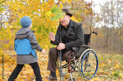 Young boy playing with his disabled grandfather