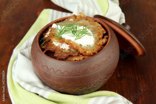 Potato pancakes in pot, on wooden background
