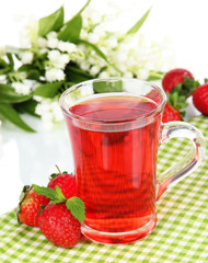 Delicious strawberry tea on table on white background