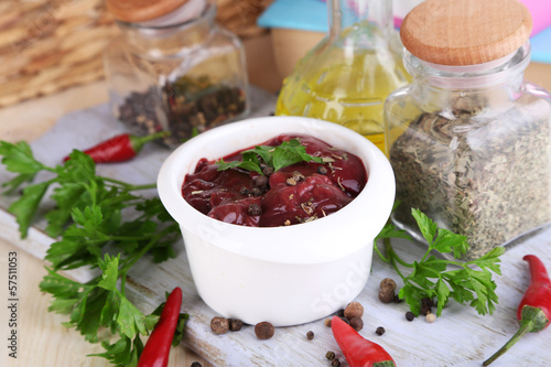 Raw liver in bowl with spices and condiments