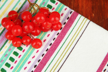 Red berries of viburnum on napkin on wooden background