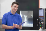 Portrait of confident technician with clipboard in front of lathe cutting machine in hi-tech manufacturing plant