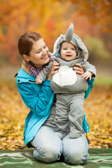 Young woman and baby boy in elephant costume in autumn park