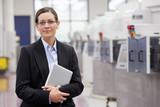 Portrait of smiling businesswoman holding digital tablet in hi-tech manufacturing plant