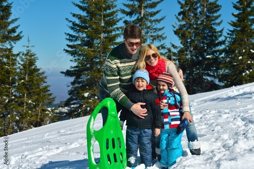 family having fun on fresh snow at winter