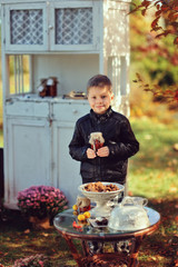 in the autumn garden stands a boy on a background of white furni