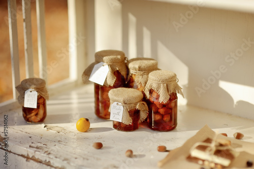 in the rays of sunlight on the white buffet jars of jam, berries