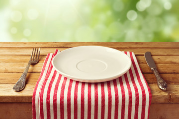 Empty plate with knife and fork on tablecloth