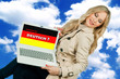 woman holding laptop with german language sign