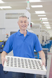 Portrait of smiling engineer holding finished machine parts in manufacturing plant