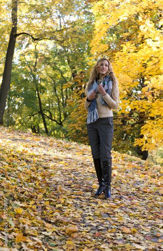 The young beautiful blond woman is walking in autumn park
