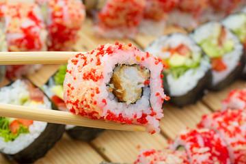 Sushi roll in tempura and red tobiko in chopsticks