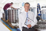 Portrait of serious manager with clipboard in steel bearing manufacturing plant