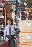 Portrait of confident businessman holding digital tablet and leaning on crates in warehouse
