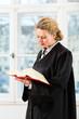Anwältin in Kanzlei mit Gesetzbuch