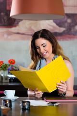 Frau im Cafe oder Restaurant mit Speisekarte