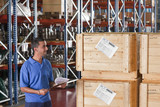Smiling worker holding clipboard and checking crates in warehouse