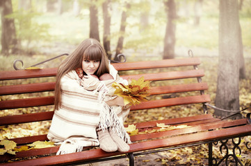 Beautiful young woman sits on a bench in an autumn park