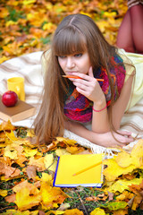 Beautiful girl with notebook on a background autumn leaves