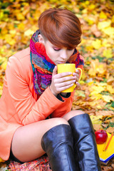 Young beautiful woman that drinks tea on a background autumn