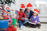 Siblings And Father Reading Book By Christmas Presents