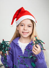 Girl In Santa Hat Holding Fairy Lights