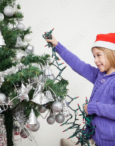 Girl Decorating Christmas Tree With Fairy Lights