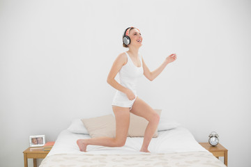 Laughing woman playing air guitar while listening to music