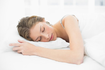 Relaxed young woman sleeping under the cover on her bed