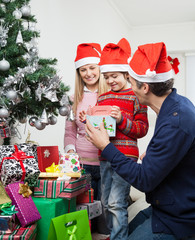 Parents Giving Gift To Boy By Christmas Tree