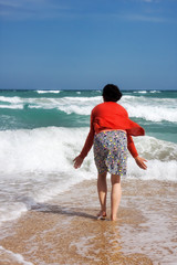 Happy woman stands in the sea beach
