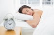 Sleeping woman with blurred alarm clock on bedside table