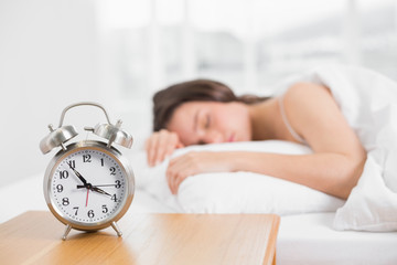 Woman in bed with alarm clock in foreground